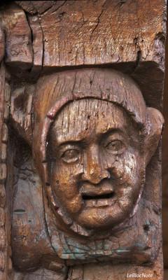 Tête sculptée sur une poutre