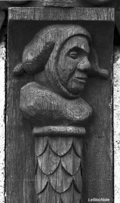 Tête en bois sculptée sur une poutre