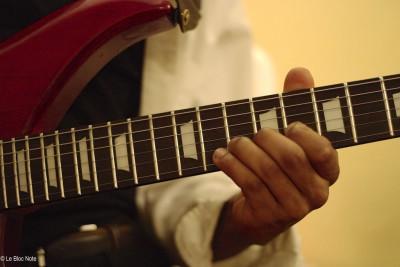 Main d'un guitariste sur le manche de son instrument